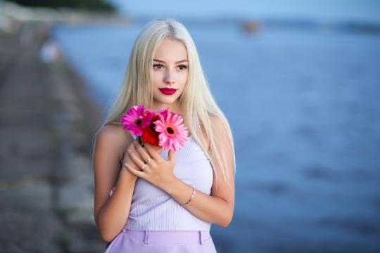 美人拿着花在海边淡淡的微笑